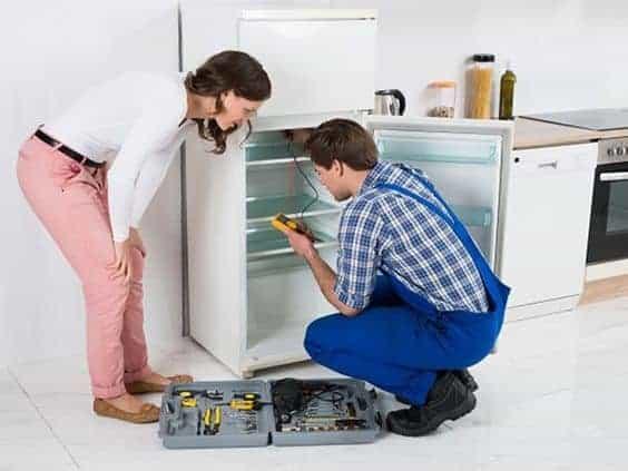 мастер чинит холодильник
